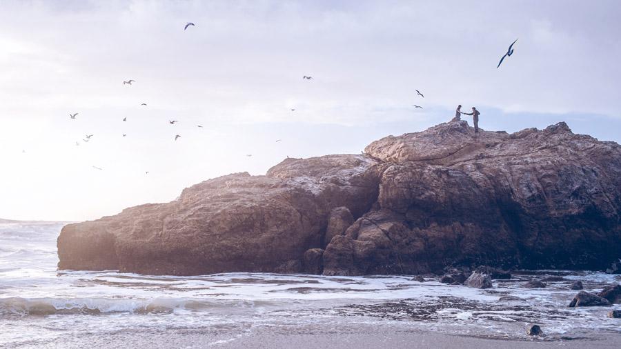フリー写真 海岸の岩と手をつなぐカップル