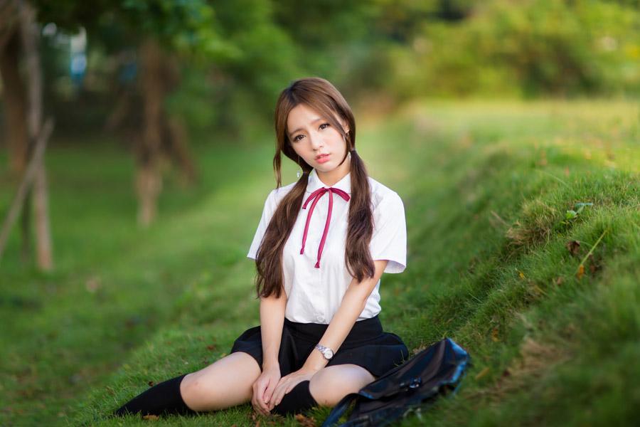 フリー写真 制服姿で芝生の上に座る女子学生