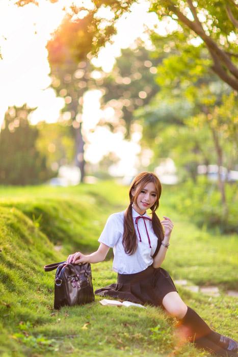 フリー写真 芝生の上に座って本を開けている女子学生