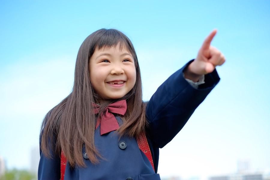 フリー写真 青空と指差す小学生の女の子