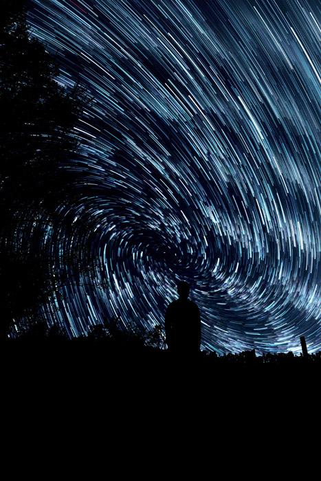 フリー写真 渦を巻く星の軌跡と人のシルエット