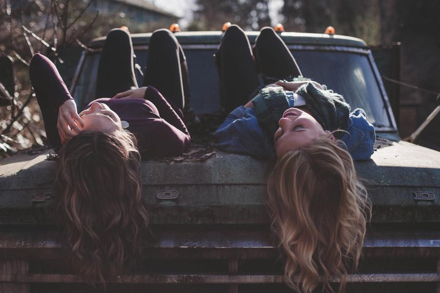 フリー写真 放置された車の上に寝転ぶ二人の女性