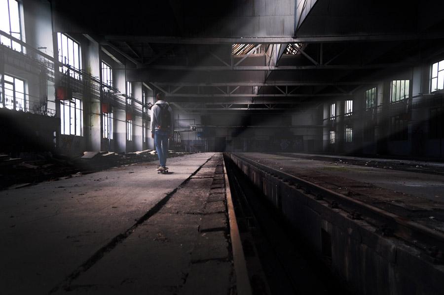 フリー写真 廃墟の工場跡でスケボーする少年