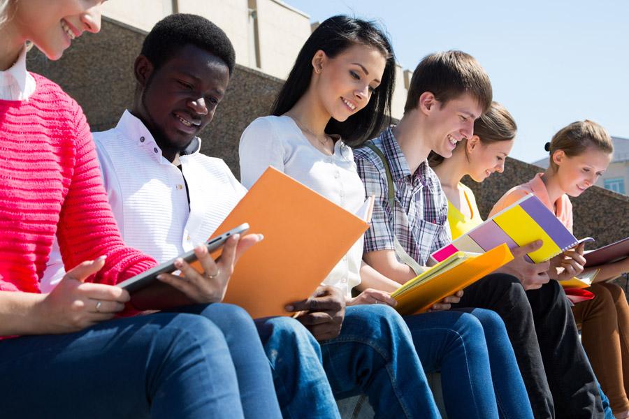 フリー写真 ノートやタブレットPCを見ている大学生のグループ