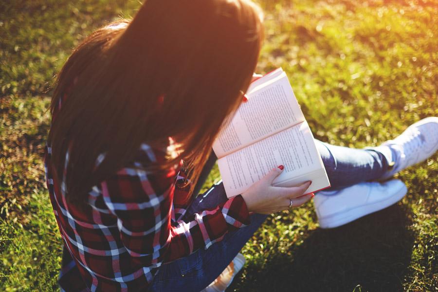 フリー写真 芝生の上で本を読む女性
