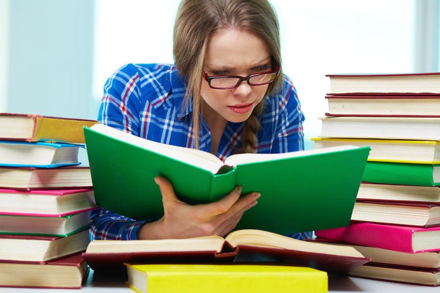 フリー写真 本に囲まれて読書に夢中の女子大学生