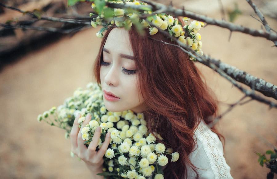 フリー写真 木の枝と花束を抱きしめるベトナム人女性