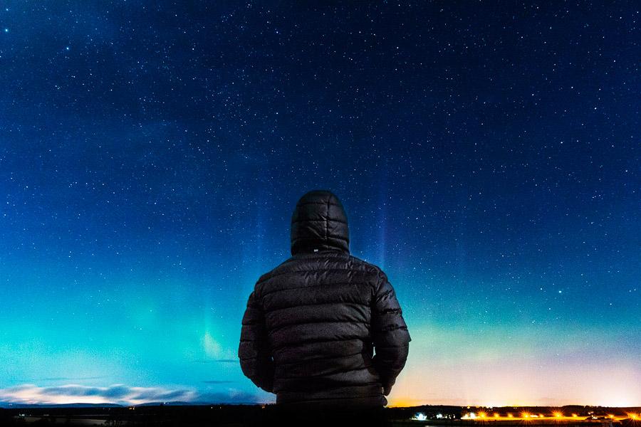 フリー写真 オーロラと星を眺める人物の後ろ姿