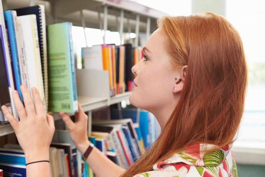 フリー写真 本を探す女子大学生の横顔