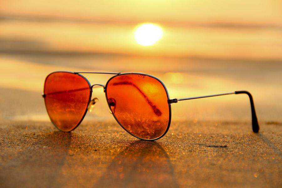 フリー写真 砂浜の上に置かれたサングラスと夕日