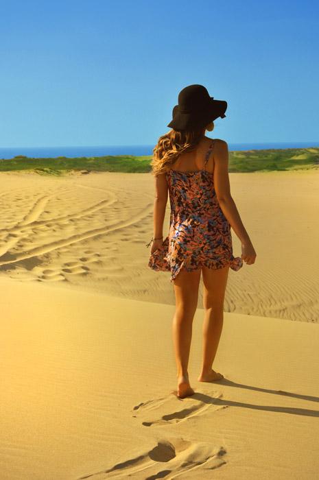フリー写真 砂浜の上を歩く外国人女性の後ろ姿