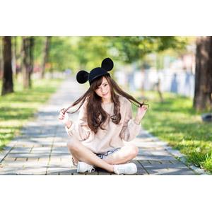 フリー写真, 人物, 女性, アジア人女性, 女性(00160), 中国人, ミッキー帽子, 座る(地面), あぐらをかく, 髪の毛を触る