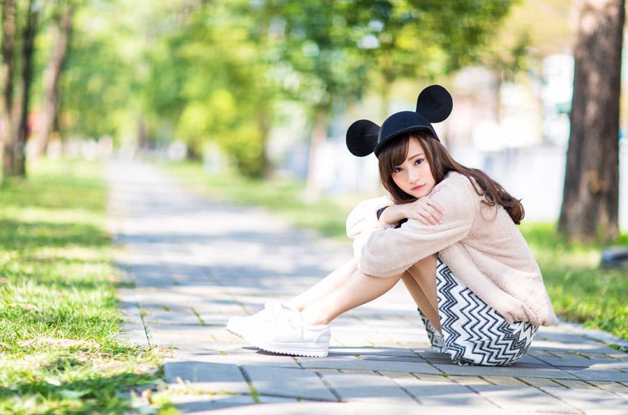 フリー写真 ミッキー帽を被って体育座りしている女性