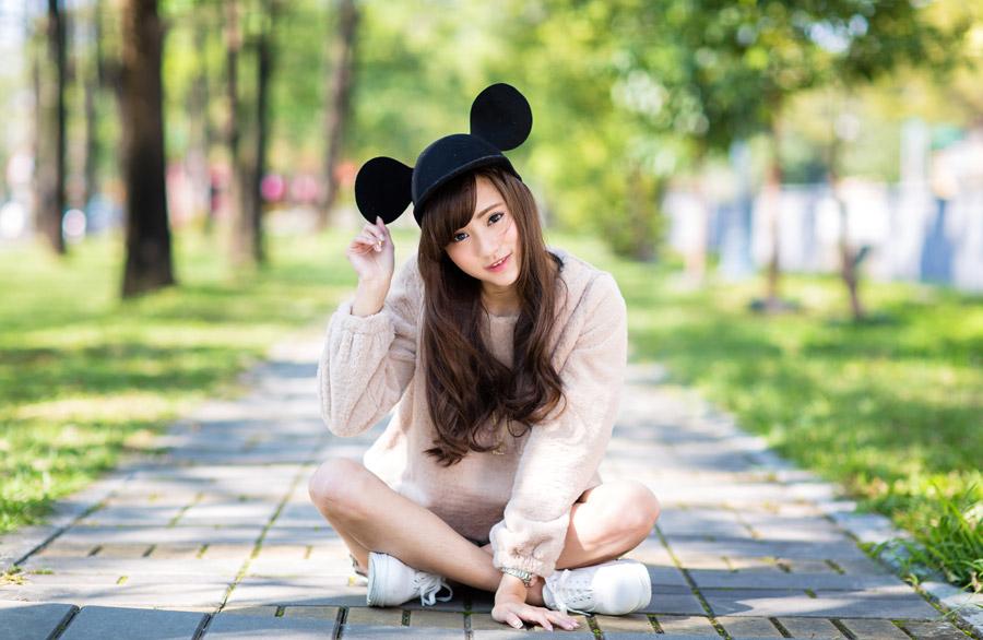 フリー写真 ミッキー帽を被って地面に座る女性