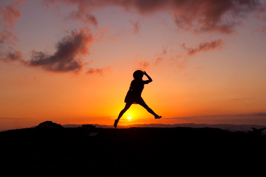 フリー写真 夕日とジャンプする女性のシルエット
