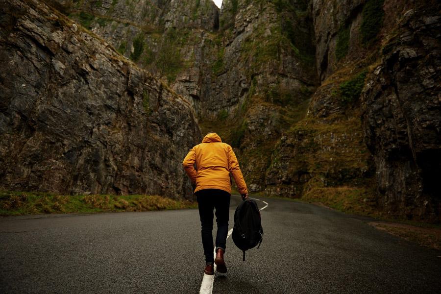 フリー写真 岩山と道路を歩く人物の後ろ姿