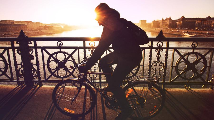 フリー写真 夕日と自転車で橋を渡る男性