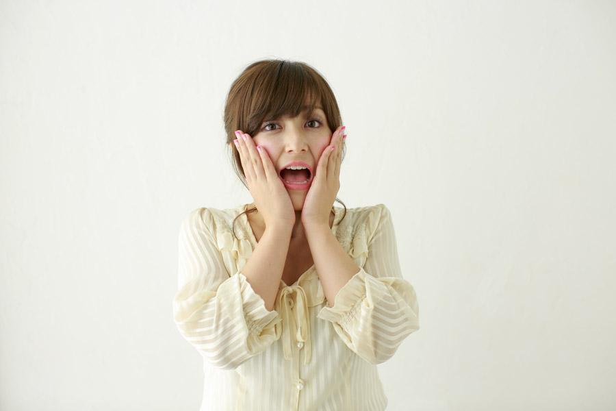 フリー写真 頬に手を当てて驚く日本人女性
