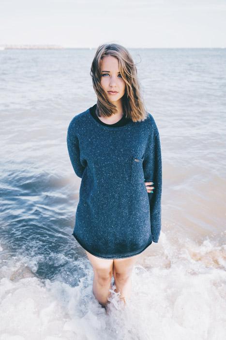 フリー写真 海の浅瀬に立つ外国人女性