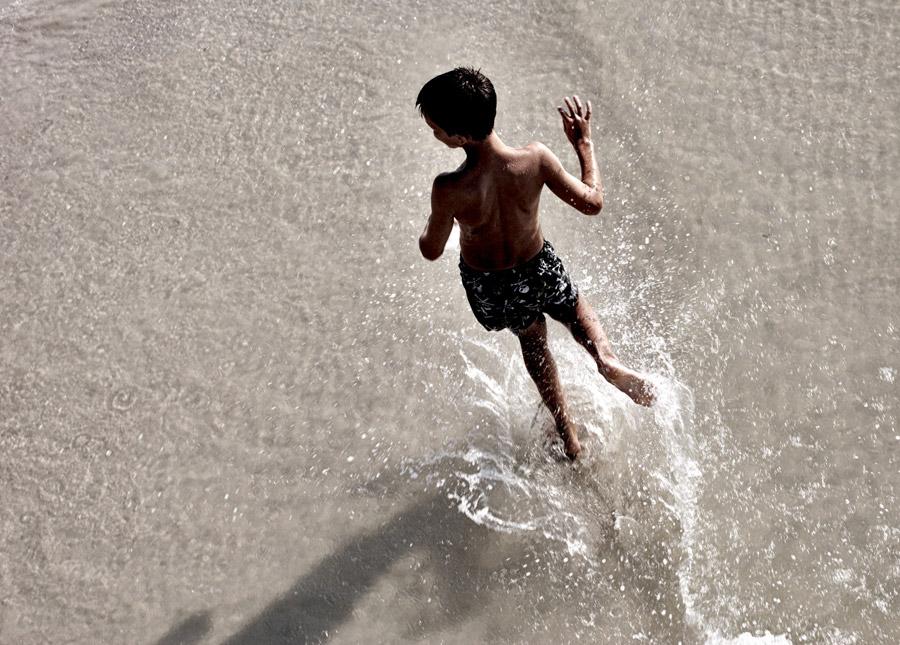 フリー写真 水しぶきを上げてはしゃぐ男の子