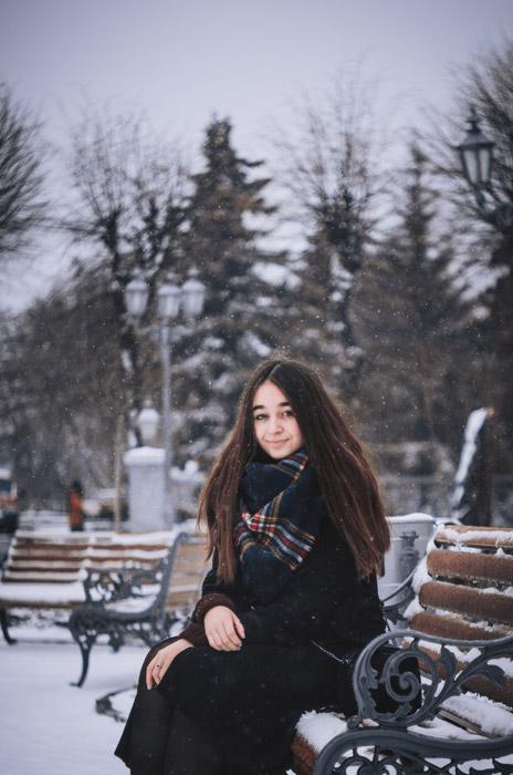 フリー写真 雪の降るベンチに座っている外国人女性