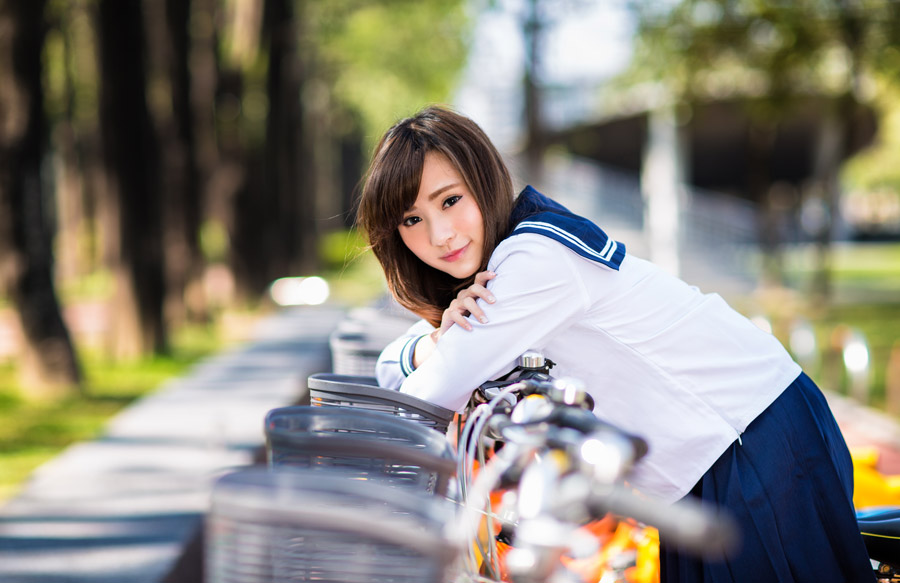 フリー写真 自転車のカゴに肘をついている女子高生