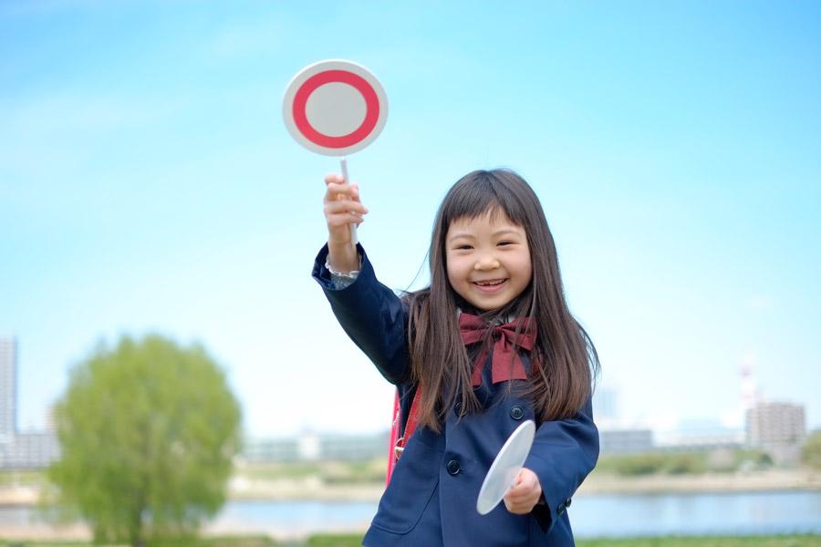 フリー写真 マルの札を上げる小学生の女の子