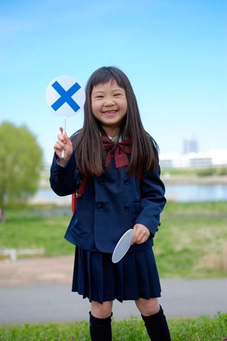 フリー写真 バツの札を上げる小学生の女の子
