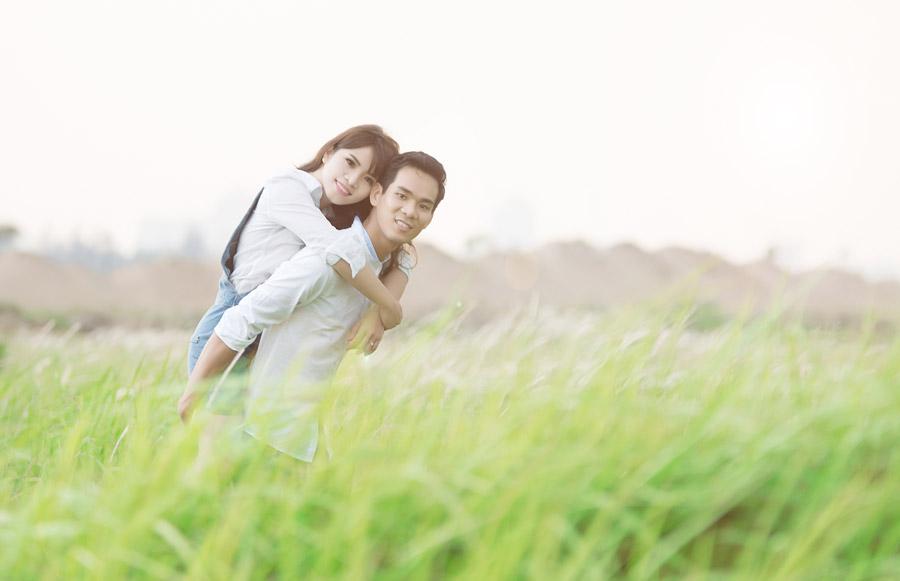 フリー写真 草むらでとおんぶしているカップル