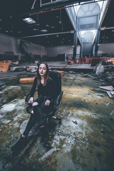 フリー写真 廃墟の建物と椅子に座る外国人女性