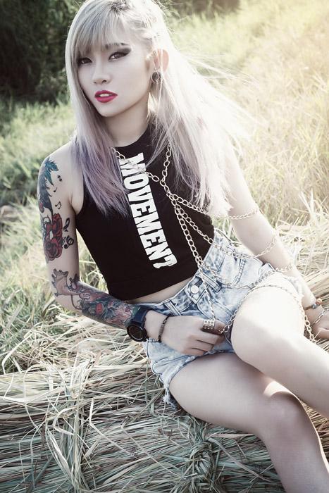 フリー写真 干し草の上に座る刺青の女性