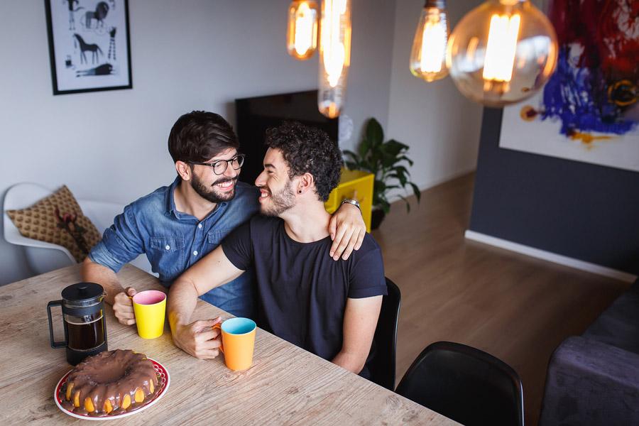 フリー写真 食卓に座って肩を組む男性カップル