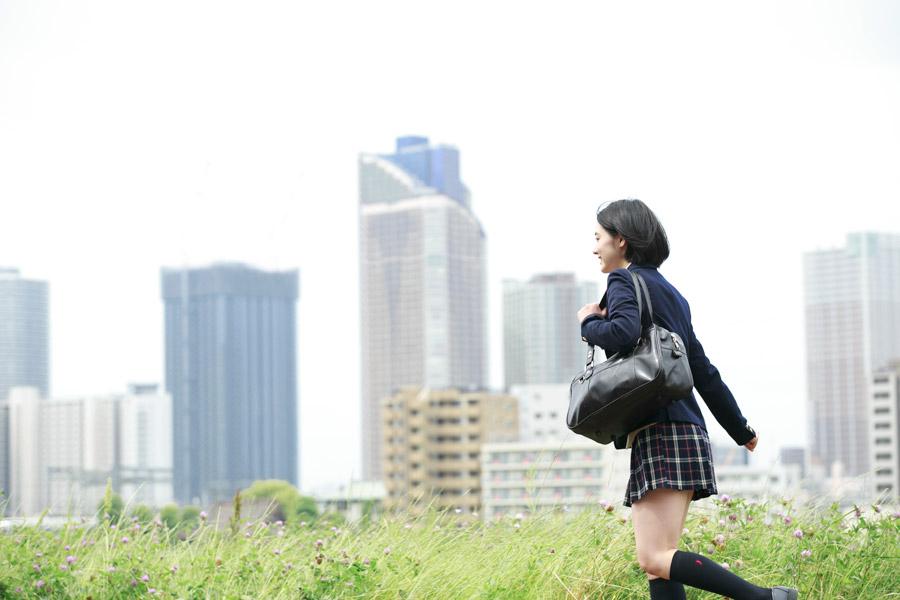 フリー写真 高層ビルと通学途中の女子高生