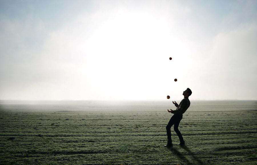 フリー写真 霧のかかる牧草地でジャグリングしている男性