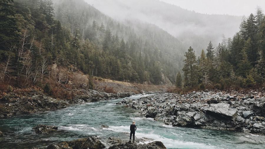 フリー写真 霧に包まれる山と川岸に立つ男性