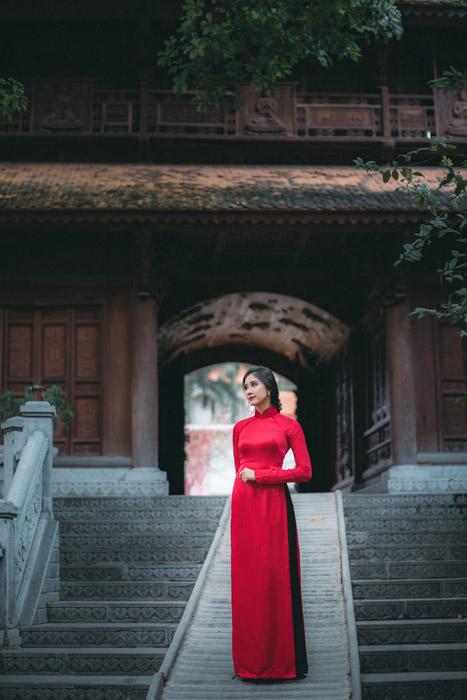 フリー写真 アオザイ姿で山門の前に立つベトナム人女性