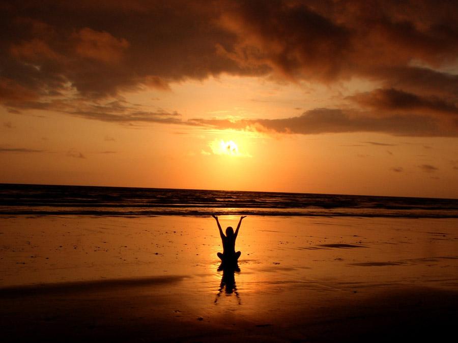 フリー写真 夕暮れのビーチに座る女性のシルエット