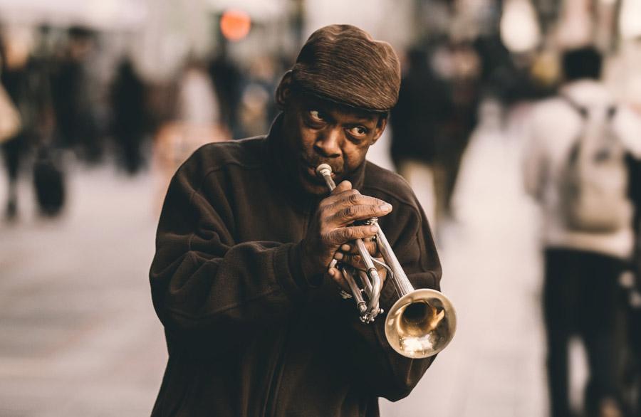 フリー写真 街中でトランペットを吹いている黒人男性