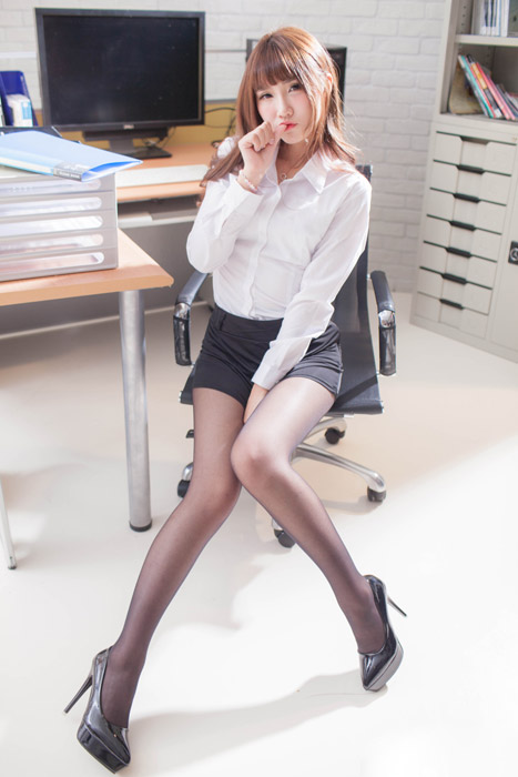 フリー写真 オフィスチェアに座って指を咥えるOL