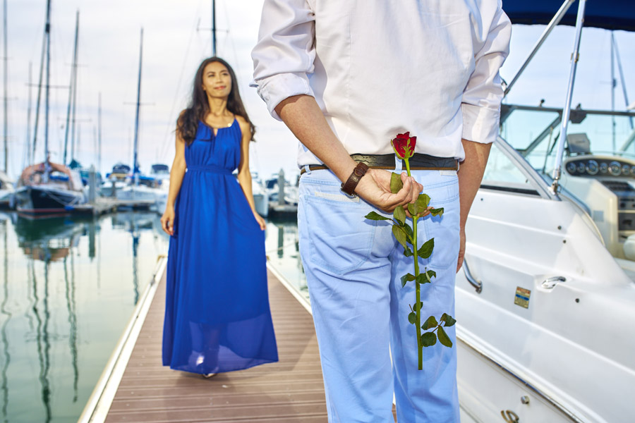フリー写真 彼女にプレゼントする花を隠し持つ彼氏