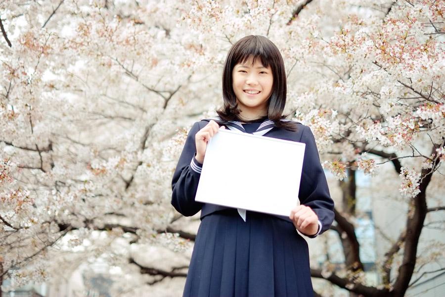 フリー写真 桜の花とメッセージボードを持つ女子高生