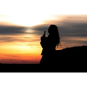 フリー写真, 人物, 女性, 武器, 銃(鉄砲), 拳銃, ピストル, シルエット(人物), 人と風景, 夕暮れ(夕方), 夕焼け
