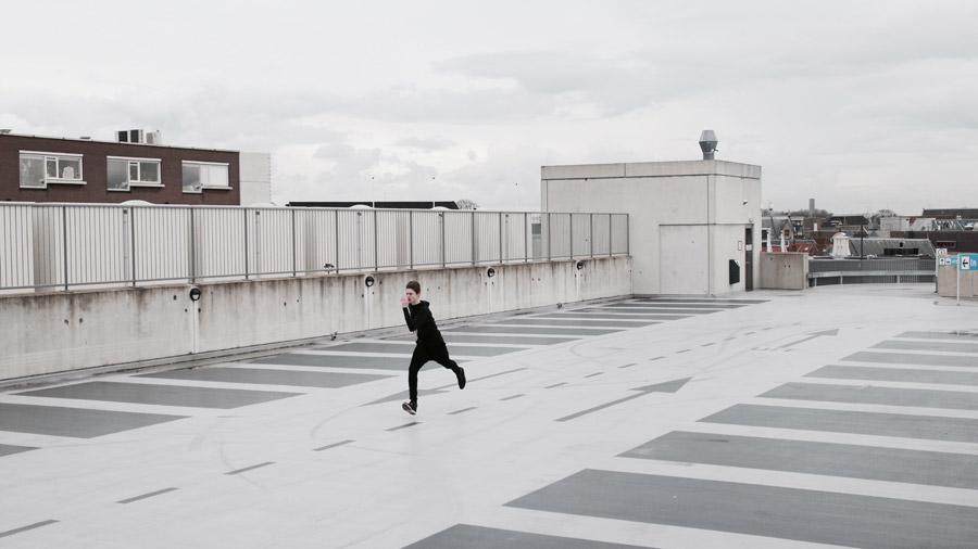 フリー写真 屋上の駐車場を走る外国の男性