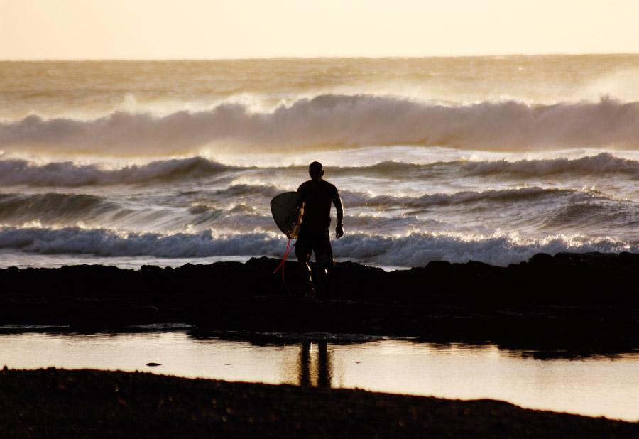 フリー写真 波とサーフボードを担ぐ男性