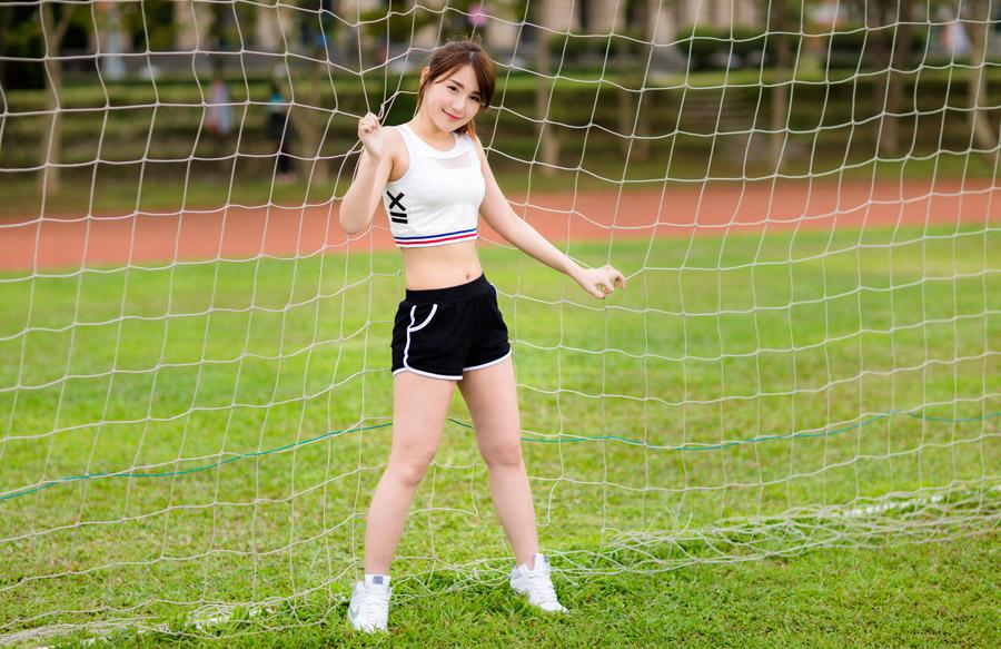 フリー写真 サッカーのゴールネットとスポーツウェア姿の女性