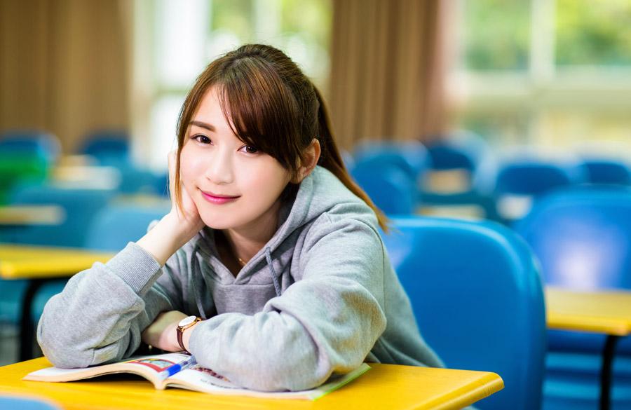 フリー写真 大学の教室で頬杖をついている女子大学生