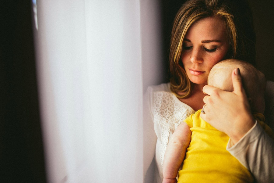 フリー写真 赤ちゃんを抱きながら目を閉じる母親