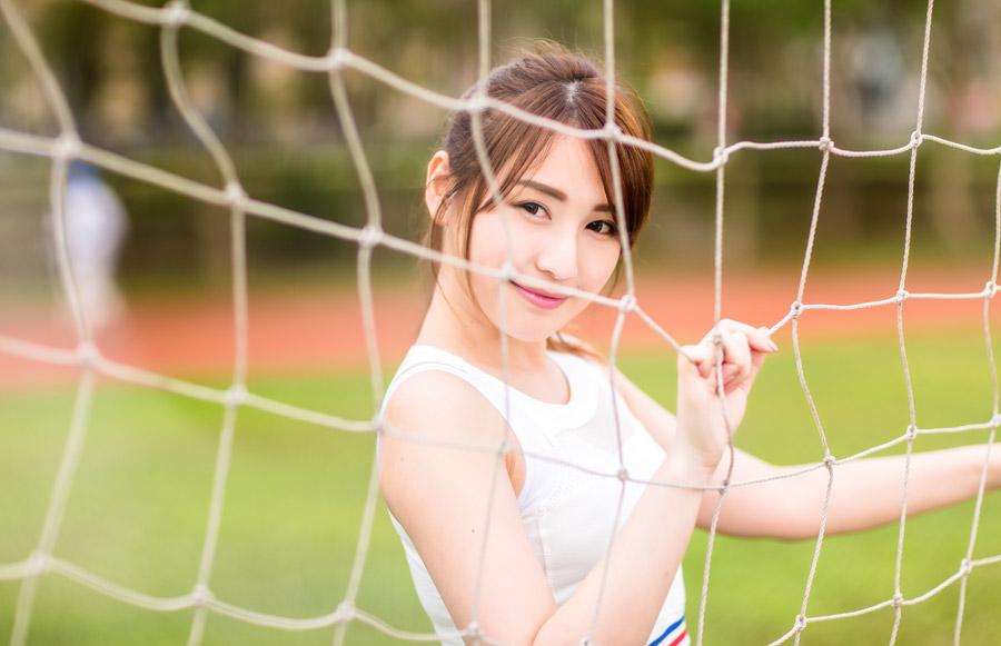 フリー写真 サッカーのゴールネット越しの女性ポートレイト