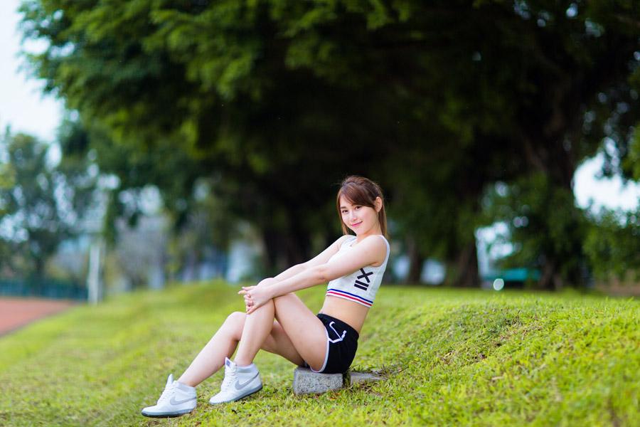 フリー写真 スポーツウェア姿で膝を抱えて座る女性