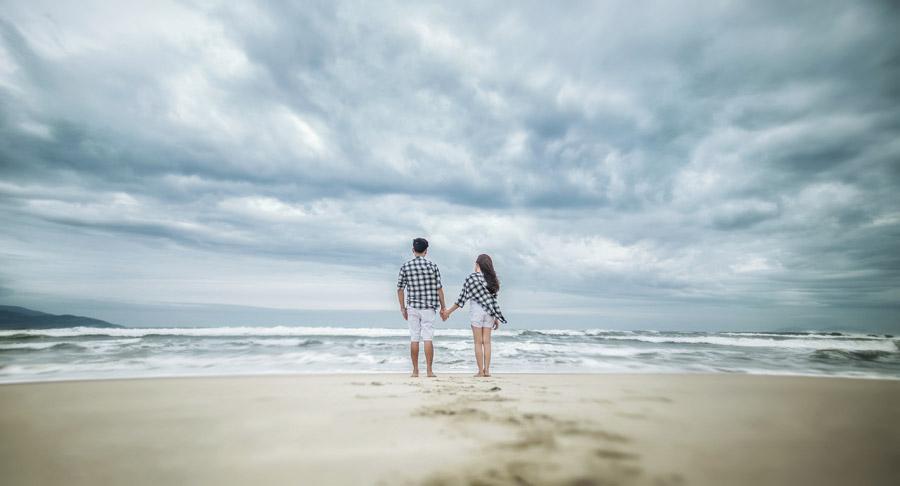 フリー写真 砂浜で手をつなぐカップルの後ろ姿
